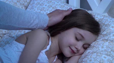 devanear : Man strokes his daughters head, she sleeps. Close up Stock Footage