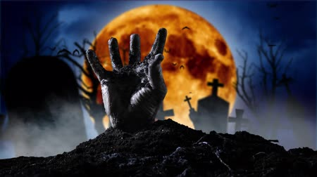 zombi : Zombie hand coming out of the grave. Graveyard smoky background Stok Video