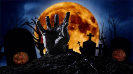 tüm : Zombie hand coming out of the grave on the background of the halloween pumpkin Stok Video