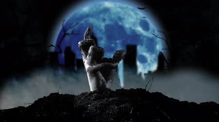 doom : From the grave slowly emerging human hand in the background cemetery and moon. Smoky background