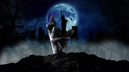 bat : Hand of a zombie comes out of the ground from behind silhouettes of houses and statue of Liberty. Smoky background Stock Footage