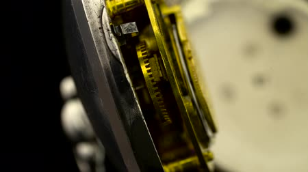 going round : Working mechanism of the clock gear closeup rotate . Black background. Close up . Sound
