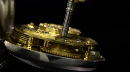 windup : Wind up the clock old key mechanism. Close up. Black background. Sound Stock Footage