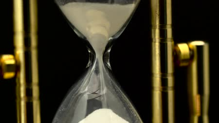 темно : Hourglass is flowing and suddenly stop. Close up. Black background