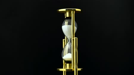 ampulheta : Time passing while sand falls through hourglass. Black background Stock Footage