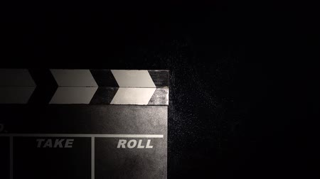 arduvaz : Person uses movie clapper board on black close up