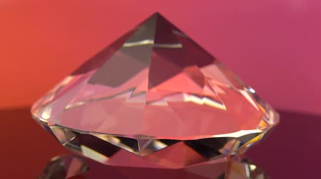 facets : Crystal clear brilliant cut diamond standing on its point rotates