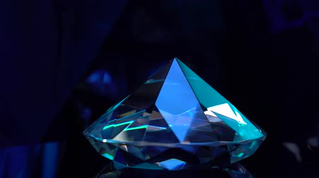 faceta : One diamond turns and shimmers in blue colors
