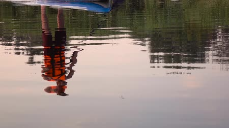remo : Reflection of a guy in the water who rows in an inflatable raft. Slow motion