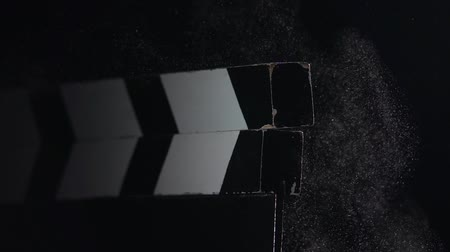 мел : Film slate being clapped . Close up. Black background. Slow motion