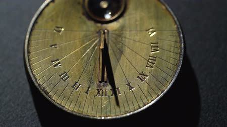going round : Sundial from the rays of the sun show time. Black background. Close up Stock Footage