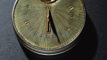 going round : Solar pocket watch running from the rays of the sun . Black background. Close up