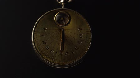 going round : Sundown antique clock shows time . Black background. Close up