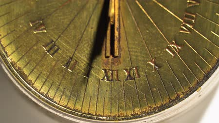 going round : Sundial shows time from bright rays. White background. Close up