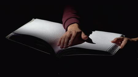 blindness : Man reading a book for the blind in a dark room . Close up