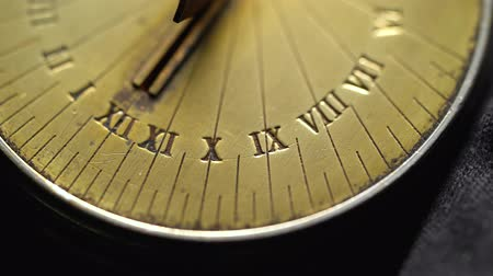 going round : Solar vintage clock rotate. Black background. Close up