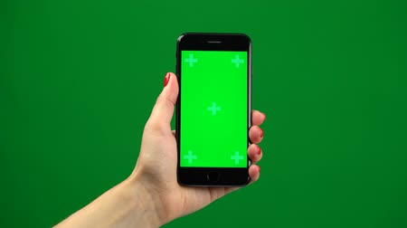 vertically : Female hand holding the newest smartphone on green screen