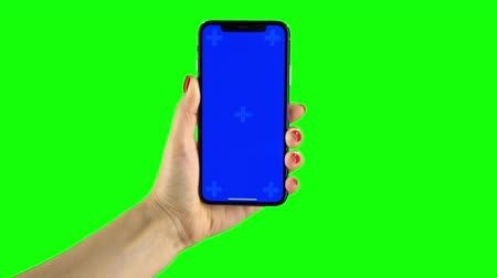 vertically : Holding hand a mobile smartphone blue screen. Green screen
