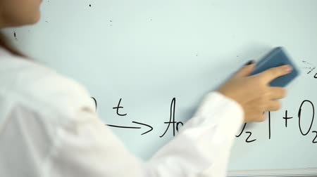 borracha : Girl erases chemistry formulas from the board Stock Footage