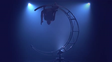 sznurek : Gymnast hangs upside down in a twine on a rotating metal construction moon. Blue smoke background