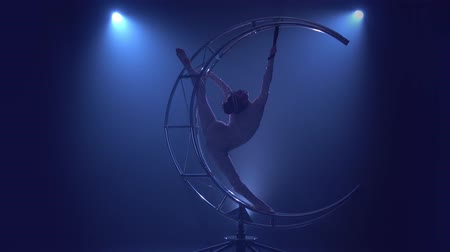 akrobata : Gymnast rotates on a metal structure moon in a vertical string. Blue smoke background