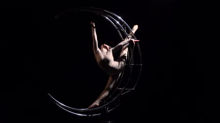 paaldans : Gymnast rotates on a metal structure moon in a vertical string. Black background