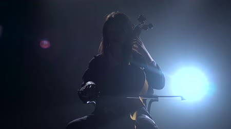 houslista : Musician in a dark room sits on a chair and plays the violoncello. Silhouette. Black smoke background Dostupné videozáznamy