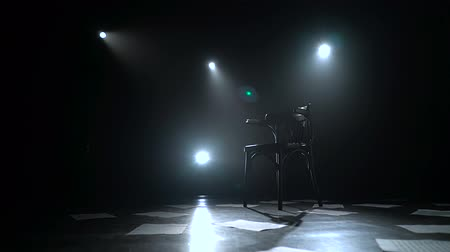 standlar : Chair stands in the middle of a dark studio with lanterns on the floor sheets scattered. Black smoke background