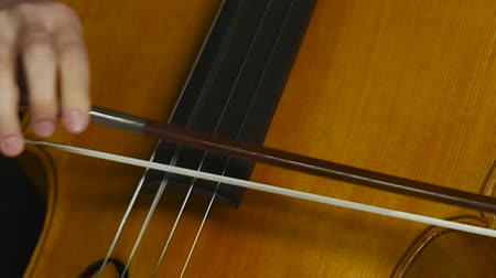 opus : Cello musical instrument close up bowing on strings. Clos up. Black smoke background