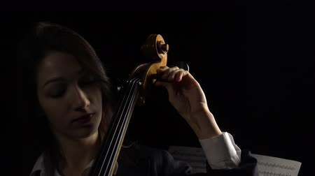 opus : Girl tunes a cello. Black background. Close up