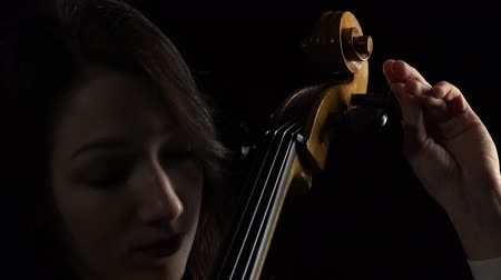 виолончель : Musician tunes a cello. Black background. Close up