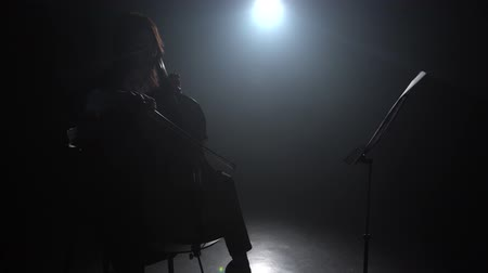 rehearsing : Playing the cello in a dark room with a lantern next to the music stand. Silhouette. Black smoke background