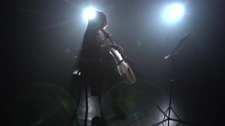 rehearsing : Glare from the light in a room girl plays the cello. Silhouette. Black smoke background