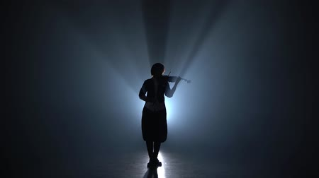 луки : Girl plays the violin a classic composition in a dark smoky room. Silhouette. Black smoke background