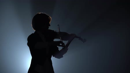 hegedűművész : Violinist plays a lyrical work. Black smoke background. Close up. Silhouette
