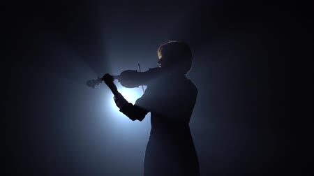 Girls standing back and playing on violins in a dark room. Black smoke background. Back view