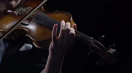 Violinist holds a bow and plays . Black background. Close up