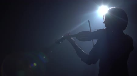 луки : Dark scene with a violinist she bows on strings glare around the room. Black smoke background. Back view