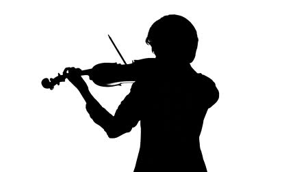 szakadt : Violinist plays a classic work. White background. Silhouette. Slow motion