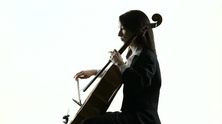 hegedűművész : Female hand plays on a cello in white studio music sheets. White background. Side view. Slow motion Stock mozgókép