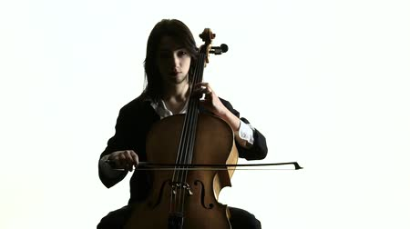 виолончель : Woman plays the cello music on white studio. White background. Slow motion Стоковые видеозаписи