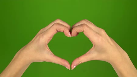 simbolismo : Romantic love sign with hands on green screen