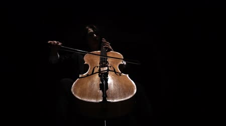 kordon : Girl in a dark room plays a cello rehearsing a composition. Black background. Bottom view Stok Video