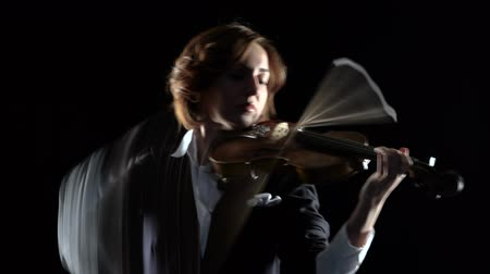 houslista : Violinist performs a violin in a black studio. Black background