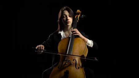 professionally : Woman plays the cello on dark studio. Black background Stock Footage