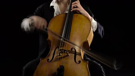 виолончель : Girl in a dark room plays a cello rehearsing a composition. Black background