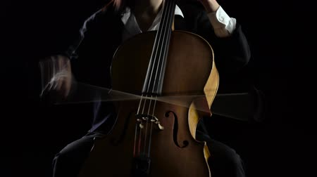 teljesítmény : Cellist playing a musical composition .Black background Stock mozgókép
