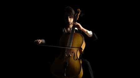 opus : Girl plays the cello on dark studio. Black background Stock Footage