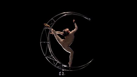 acrobate : Gymnast a rotates on a metal structure moon in a vertical string. Black background. Slow motion Vidéos Libres De Droits