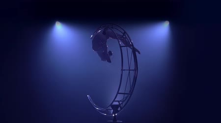 acrobate : Graceful in a brilliant costume performs tricks on a special design in a dark room. Blue smoke background. Slow motion Vidéos Libres De Droits